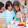Happy family using laptop during the breakfast — Stock Photo