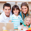 Loving family using laptop during the breakfast — Stock Photo