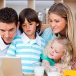 Lovely family using laptop during the breakfast — Stock Photo