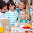 Photo: Blissful family using laptop during the breakfast