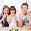 图库照片: Hungry family eating burgers in the living room