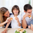 Loving family eating burgers in the living room — Stock Photo #10294666