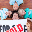 Stock Photo: Happy family lying on floor after buying a house