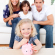 Blond little girl inserting coin in a piggybank - Stock Photo