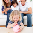 Adorable little girl inserting coin in a piggybank — Stock Photo #10294678