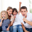Portrait of a lively family singing through microphone — Stok fotoğraf