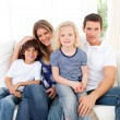Joyful family watching television sitting on sofa — Stok fotoğraf