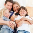 United family watching television sitting on sofa — Stockfoto