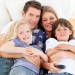 Кавказский семья смотрит телевизор, сидя на диване — Стоковое фото