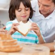 Little boy eating a sandwich with his father — Stock Photo