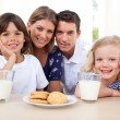 Children eating biscuits and dinking milk with their parents - Stock Photo