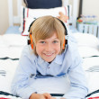 Stock Photo: Smiling blond boy listening to music