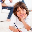 Smiling little boy drawing lying on floor — Stock Photo