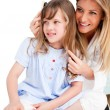 Charming woman brushing her daugther's hair — Stock Photo