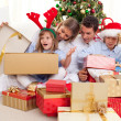 Stock Photo: Portrait of happy family unpacking Christmas presents
