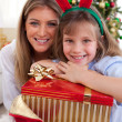 Portrait of a mother and her daughter holding Christmas presents — Stock Photo