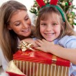 Smiling mother and her daughter holding Christmas gifts — Foto de Stock