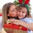 Loving mother kisses daughter at Christmas — Stock Photo