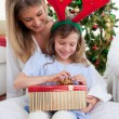 Portrait of a mother and her daughter unpacking Christmas gifts — Stock Photo