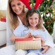 Smiling mother and her daughter unpacking Christmas gifts - Foto Stock