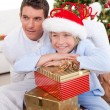 Smiling father and his son holding Christmas gifts — Stock Photo