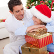 Smiling father and his son unpacking Christmas gifts — Stock Photo