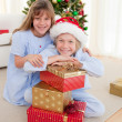 Happy brother and sister holding Christmas presents — Stock Photo