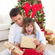 Foto Stock: Surprised little girl opening presents with her father