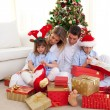 Portrait of a happy family opening Christmas gifts — Stock Photo