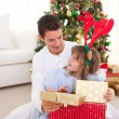 Smiling father and his daughter opening Christmas gifts — Stock Photo