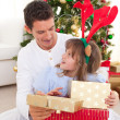 Portrait of a smiling father and his daughter opening Christmas — Stock Photo #10294763