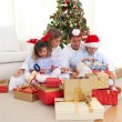 Young family unpacking Christmas presents — Stock Photo