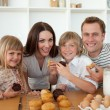 Cute children eating muffins with their parents - Foto Stock