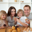 Cute children eating muffins with their parents - Zdjęcie stockowe