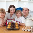 Cheerful family presenting their muffins — Stock Photo
