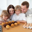 Jolly family presenting their muffins — Stock Photo
