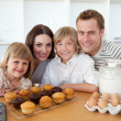 Happy family presenting their muffins - Foto Stock