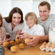 Smiling family eating their muffins in the kitchen — Stock Photo