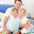 Cheerful father and his children holding a terretrial globe — Stock Photo