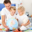 Jolly father and his children holding a terretrial globe — Stock Photo