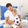 Adorable little boy and his father playing with a soccer ball — Stock Photo #10294905