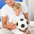 Blond little boy and his father playing with a soccer ball — Stock fotografie