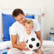 Cute little boy and his father playing with a soccer ball — Stock Photo
