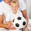 Smiling little boy and his father playing with a soccer ball — Stock Photo #10294912