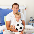 Portrait of a little boy and his father playing with a soccer ba — Stock Photo #10294913