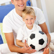 Stock Photo: Close-up of a little boy and his father playing with a soccer ba
