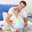 Smiling father and his son looking at a terretrial globe — Stock Photo