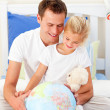 Earing father and his daugther looking at terrestrial globe — Stock Photo #10294921