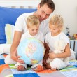 Blond siblings and their father looking at a terrestrial globe — Stock Photo