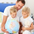 Adorable children and their father looking at a terrestrial glob — Stock Photo